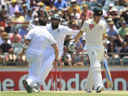 South Africa's Dale Steyn (L) and Hashim Amla (C) celebrate the wicket of Australia's captain Michael Clarke (R) at the WACA during the second day's play of the third test cricket match in Perth December 1, 2012. REUTERS/Stringer