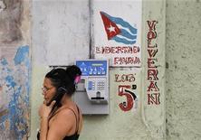 """El Gobierno de Cuba ha rebajado el coste de las llamadas telefónicas entre Estados Unidos y la isla, dijo el viernes una nota oficial que no aclaró las cifras, en una medida que busca """"beneficiar"""" la comunicación entre los cubanos y su emigración. En la imagen de archivo, una mujer habla por teléfono en La Habana, el 29 de junio de 2010. REUTERS/Desmond Boylan"""