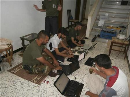 Members of the Free Syrian Army, under the name of Farouq Brigades, use laptop computers in Homs August 18, 2012. Picture taken August 18, 2012. REUTERS/Shaam News Network/Handout/Files