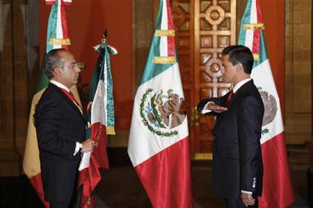 Mexico's outgoing President Felipe Calderon (L) holds the national flag as Mexico's new President Enrique Pena Nieto salutes during a midnight handover ceremony at the Palacio Nacional in Mexico City December 1, 2012. REUTERS/Presidencia de Mexico/Handout