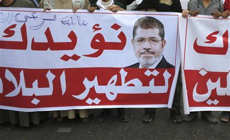 Pro-Mursi protesters chant slogans in support of Egypt's President Mohamed Mursi while carrying a banner that reads, ''We support you to purify the country'' in Cairo December 1, 2012. Islamist crowds demonstrated in Cairo on Saturday in support of President Mohamed Mursi, who is racing through a constitution to try to defuse opposition fury over his newly expanded powers. REUTERS/Asmaa Waguih