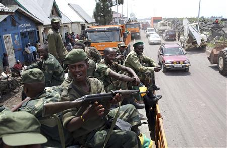 M-23 rebel fighters are seen on a truck as they withdraw from Goma December 1, 2012. Rebel fighters, singing and brandishing weapons, pulled out of Democratic Republic of Congo's eastern border city of Goma on Saturday, raising hopes regional peace efforts could advance negotiations to end the insurgency. REUTERS/Goran Tomasevic