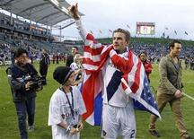 Los Angeles Galaxy's David Beckham gives a thumbs up to the crowd next to his son Romeo after Galaxy defeated the Houston Dynamo to win the MLS Cup championship soccer game in Carson, California, December 1, 2012. REUTERS/Danny Moloshok