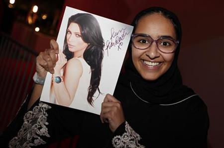 A Saudi fan holds a picture of U.S. television celebrity Kim Kardashian, for her autograph during her promotional visit to a newly built shopping mall in Riffa, south of Manama December 1, 2012. REUTERS/Hamad I Mohammed