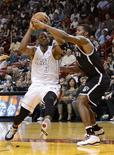 Miami Heat's Dwyane Wade (L) is defended by Brooklyn Nets's Joe Johnson during the first half of their NBA basketball game in Miami, Florida, December 1, 2012. REUTERS/Rhona Wise