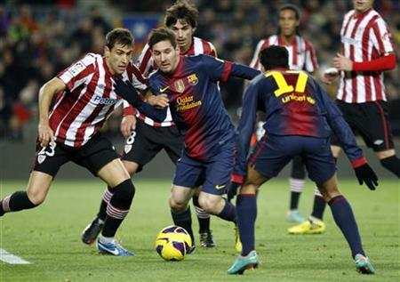Barcelona's Lionel Messi (C) is challenged by Athletic Bilbao players before scoring his second goal during their Spanish first division soccer match at Nou Camp stadium in Barcelona December 1, 2012. REUTERS/Gustau Nacarino