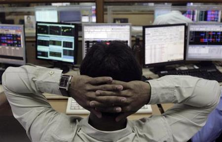 A broker monitors share prices at a brokerage firm in Mumbai August 8, 2011. REUTERS/Stringer