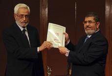"""El presidente egipcio, Mohamed Mursi, convocó un referéndum el 15 de diciembre sobre un borrador de nueva Constitución e instó a un diálogo en el país sobre las """"preocupaciones de la nación"""" mientras Egipto se acerca al término de la transición tras el fin del gobierno de Hosni Mubarak. En la imagen, el juez Hosam El Gheriany, presidente de la asamblea constitucional, entrega a Mursi el borrador final de la constitución egipcia, en El Cairo, el 1 de diciembre de 2012. REUTERS/Egyptian Presidency/Handout"""