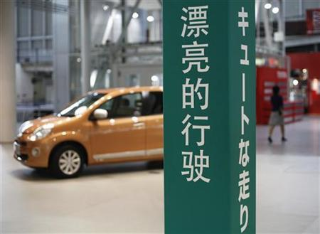 A visitor walks past a Toyota Motor Corp's car displayed behind a sign in both Chinese (L) and Japanese at the company's showroom in Tokyo October 18, 2012. REUTERS/Toru Hanai