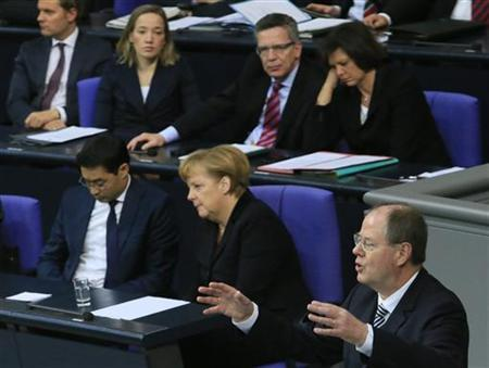 German Chancellor Angela Merkel and Leader of Germany's liberal Free Democrats FDP and Economy Minister Philipp Roesler listen to the speech of Peer Steinbrueck of the opposition Social Democratic Party (SPD) during a session of the lower house of parliament Bundestag in Berlin November 9, 2012. REUTERS/Tobias Schwarz