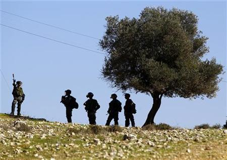 Israeli security officers stand near a tree during clashes with Palestinian stone-throwing protesters (unseen) at a protest against Jewish settlements, in the West Bank village of Nabi Saleh, near Ramallah November 30, 2012. REUTERS/Marko Djurica