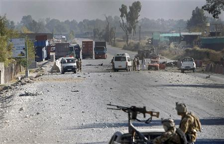 Afghan security forces inspect the site of an attack in Jalalabad December 2, 2012. Suicide attackers detonated bombs and fired rockets outside a major U.S. base in Afghanistan on Sunday, killing five people in a brazen operation that highlighted the country's security challenges ahead of the 2014 NATO combat troop pullout. REUTERS/ Parwiz