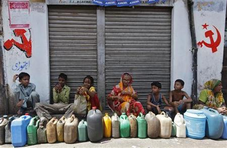 Local residents wait outside a closed ration shop with their empty containers to collect kerosene in Kolkata September 16, 2010. REUTERS/Rupak De Chowdhuri/Files