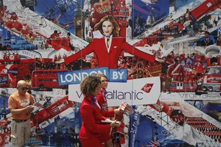 Crew members of Virgin Atlantic Airways handout flags while walking past a large placard in Union Square during a promotional event by the British owned airline to celebrate the Diamond Jubilee of Queen Elizabeth in New York June 2, 2012. REUTERS/Eduardo Munoz