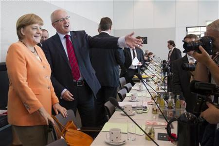 German Chancellor and leader of the Christian Democratic Union (CDU) Angela Merkel (L) and CDU faction leader Volker Kauder attends a meeting of the CDU faction before a parliamentary vote on a Spanish bank aid package in Berlin July 19, 2012. REUTERS/Thomas Peter