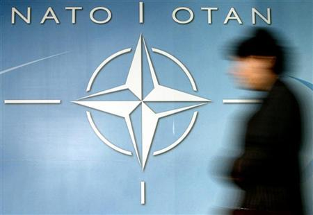 A woman walks past the NATO logo at the entrance of the Alliance headquarters ahead of a NATO foreign ministers meeting in Brussels December 4, 2003. REUTERS/Thierry Roge