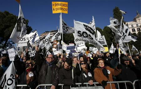 Thousands of protesters wave flags and hold signs during a rally against government cutbacks for disabled people in Madrid December 2, 2012. The flags and signs read, ''SOS disability'' and ''= Rights for diverse people'' (top). REUTERS/Andrea Comas