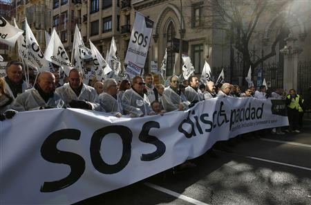 Thousands of protesters wave flags and carry a banner during a rally against government cutbacks for disabled people in Madrid December 2, 2012. The flags and the banner read, ''SOS disability''. REUTERS/Andrea Comas