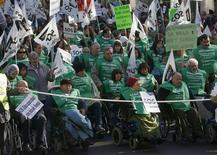 Pessoas em cadeiras de rodas carregam bandeiras e cartazes durante protesto contra cortes do governo para pessoas com deficiência em Madri, Espanha. Milhares de pessoas com deficiência e suas famílias protestaram em Madri neste domingo contra cortes de benefícios, unindo-se ao movimento de protestos contra as medidas de austeridade do governo. 02/12/2012 REUTERS/Andrea Comas