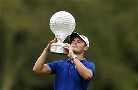 Martin Kaymer of Germany holds up the trophy after winning the 2012 Nedbank Golf Challenge in Sun City, December 2, 2012. REUTERS/Siphiwe Sibeko