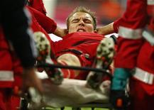 Holger Badstuber, do Bayern de Munique, geme de dor enquanto é carregado para fora do campo durante jogo do campeonato alemão em Munique, Alemanha. Badstuber passará por uma cirurgia na segunda-feira, depois de romper um ligamento cruzado do joelho direito. 01/12/2012. REUTERS/Kai Pfaffenbach
