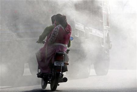 A woman on a motorcycle covers her face from smoke coming from burning garbage dump in Jammu December 7, 2009. REUTERS/Mukesh Gupta/Files