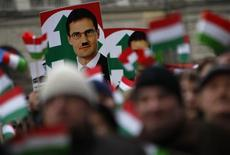 """A defaced photo of Marton Gyongyosi, a leader of Hungary's far-right political party Jobbik, is seen on a placard during a demonstration against Nazism in front of the Parliament building in Budapest December 2, 2012. The rally was held after a Hungarian far-right opposition politician urged the government to draw up lists of Jews in Hungary's Parliament and government who pose a """"national security risk"""", stirring outrage among Jewish leaders who saw echoes of fascist policies that led to the Holocaust. The government released a terse condemnation of the remarks. REUTERS/Bernadett Szabo"""