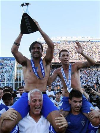 Velez Sarsfield's captain Fabian Cubero (top, L) and Ivan Bella (top, R) celebrate with the trophy after defeating Union de Santa Fe and clinching the Argentine First Division soccer championship in Buenos Aires, December 2, 2012. REUTERS/Marcos Brindicci
