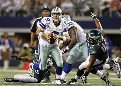 Dallas Cowboys quarterback Tony Romo scrambles as Philadelphia Eagles defensive tackle Cullen Jenkins is unable to make the tackle in the first half of their NFL football game in Arlington, Texas December 2, 2012. REUTERS/Mike Stone