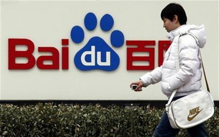 A pedestrian walks past the company logo of Baidu located outside their headquarters in Beijing March 24, 2010. REUTERS/David Gray/Files