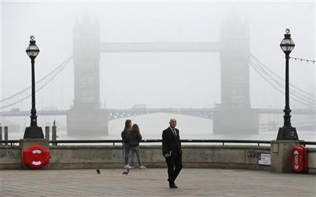 Pedestrians walk along the Thames path past Tower Bridge, on an foggy autumn morning in London October 22, 2012. REUTERS/Suzanne Plunkett (BRITAIN - Tags: CITYSPACE ENVIRONMENT)
