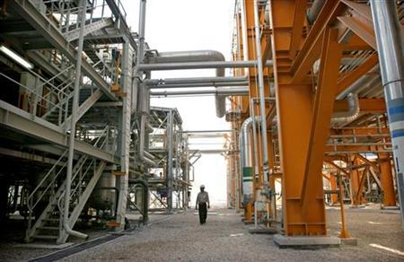 A worker walks amid facilities at phases 2-3 of the South Pars gas field, owned jointly by Iran and Qatar, are illuminated at night in Assaluyeh on Iran's Persian Gulf coast May 27, 2006. REUTERS/Morteza Nikoubazl/Files