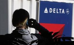 Singapore Airlines dijo el lunes que estaba en conversaciones con partes interesadas para vender su participación del 49 por ciento en la británica Virgin Atlantic, mientras algunas fuentes revelaron que Delta Air Lines está entre los potenciales interesados. En la imagen, una pasajera hablapor teléfono junto a un cartel de Delta Airlines en el aeropureto de Salt Lake City, Utah, el 21 de noviembre de 2012. REUTERS/George Frey