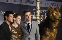 """La nueva película de vampiros adolescentes de la saga """"Crepúsculo"""" brilló nuevamente en la taquilla de Estados Unidos y Canadá, recaudando 17,4 millones de dólares en su tercer fin de semana consecutivo en el número 1 del ranking, mientras James Bond se mantuvo fuerte. En la imagen, el reparto de Crepúsculo, de derecha a izquierda Robert Pattinson, Kristen Stewart y Taylor Lautner en el estreno de """"Amanecer Parte II"""" en Alemania, el 16 de noviembre de 2012. REUTERS/Thomas Peter"""