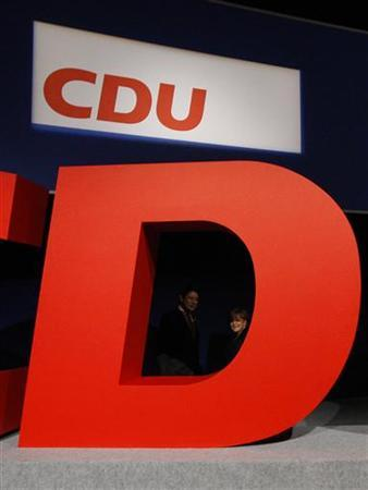 German Chancellor and leader of Germany's conservative Christian Democratic Union (CDU) Angela Merkel looks thourgh a letter of the CDU logo during a party meeting in Leipzig, November 14, 2011. REUTERS/Tobias Schwarz (GERMANY - Tags: POLITICS BUSINESS LOGO)