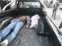 Las fuerza sirias atacaron el lunes un suburbio en manos rebeldes en Damasco con dos ataques aéreos y varias explosiones sacudieron las afueras del sur de la capital, dijeron activistas de la oposición. En la imagen, los cuerpos de un hombre y un niño, que según activistas murieron durante bombardeos de las fuerzas leales al presidente sirio Bashar el Asad, yacen en la parte de atrás de una furgoneta en Houla, cerca de Homs, el 2 de diciembre de 2012. REUTERS/Misra Al-Misri/Shaam News Network/