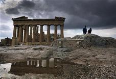 """Туристы у Парфенона в Афинах 24 октября 2012 года. Греция проведет обратный выкуп облигаций посредством модифицированного """"голландского аукциона"""", когда инвесторы заявляют, сколько они хотят продать облигаций, до того, как определена цена. REUTERS/Yannis Behrakis"""
