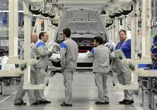 Workers of Volkswagen stand in front of a Porsche Boxter car in a production line at the Volkswagen plant in Osnabrueck, September 19, 2012. Porsche officially began production of its Boxter model at the VW plant in Osnabrueck today. REUTERS/Fabian Bimmer GERMANY (BUSINESS TRANSPORT)