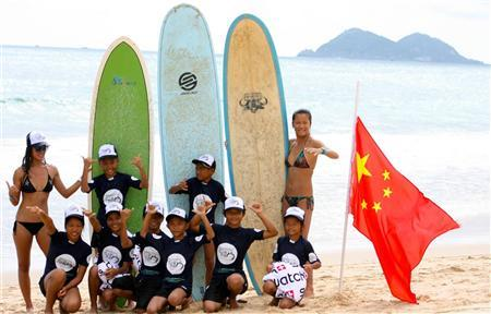 Chinese surfers Darci Liu (L) and Monica Guo (R) pose after a coaching clinic with local children at Riyuewan Bay on Hainan Island during the 2012 Swatch Girls Pro China surfing competition, in this undated handout photo taken during the November 21-25, 2012 event. REUTERS/Will Swanton/Handout