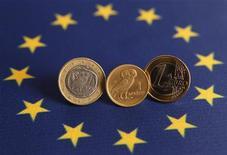 Греческая драхма между монетами в 1 евро в Стамбуле 14 июня 2012 года. Евро поднялся до максимума шести недель к доллару благодаря позитивным данным из Китая и признакам того, что Германия согласна на списание греческих долгов. REUTERS/Murad Sezer