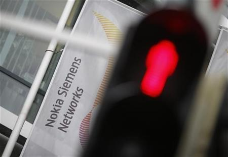 A red traffic light is pictured next to the company logo of Mobile network equipment maker Nokia Siemens Networks (NSN), in Munich November 29, 2012. REUTERS/Michael Dalder/Files