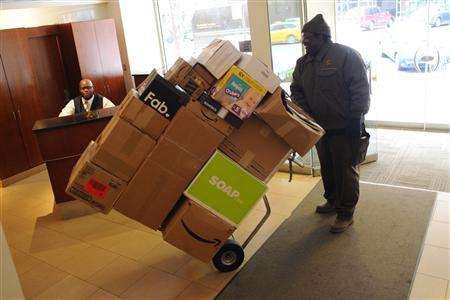 Doorman Eugene Amankwah (L) watches as USP delivery man Dion Seaberry delivers packages to the building he works in, at Central Park West in New York November 30, 2012. REUTERS/Keith Bedford