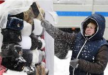 Продавщица счищает снег с сувенирных шапок-ушанок в центре Москвы, 29 ноября 2012 года. Рабочая неделя в Москве будет холодной и снежной, ожидают синоптики. REUTERS/Sergei Karpukhin