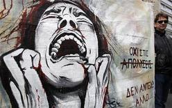 """Работник греческого муниципалитета держит плакат с надписями """"Нет увольнениям"""" (сверху) и """"Я больше не могу это терпеть"""" во время демонстрации в центре Афин 30 ноября 2012 года. Греция проведет обратный выкуп облигаций посредством """"голландского аукциона"""", что позволит ей оценить уровень спроса, прежде чем устанавливать окончательную цену сделки. REUTERS/John Kolesidis"""