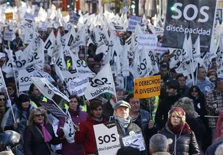 Thousands of protesters wave flags and carry banners during a rally against government cutbacks for disabled people in Madrid December 2, 2012. REUTERS/Andrea Comas