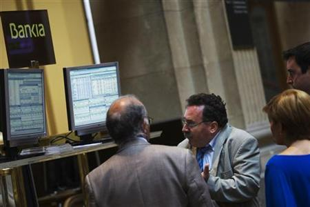 A trader (C) gestures while watching computer screens at Madrid's Bourse August 6, 2012. REUTERS/Susana Vera/Files