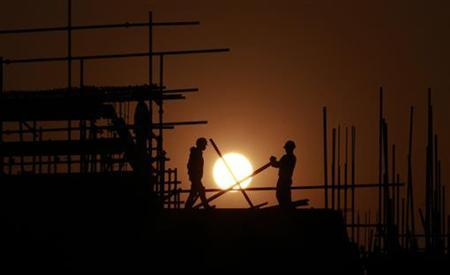 Construction workers install scaffolding on the top of a building at sunset in Shanghai November 13, 2012. REUTER/Aly Song (CHINA - Tags: BUSINESS CONSTRUCTION POLITICS TPX IMAGES OF THE DAY EMPLOYMENT)