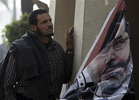 A supporter of Egyptian President Mohamed Mursi stands near a damaged picture of Mursi in front of the Supreme Constitutional Court in Maadi, south of Cairo December 2, 2012. REUTERS/Amr Abdallah Dalsh