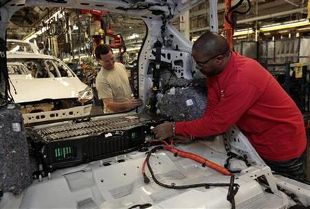 Ford Assembly workers Calvin Thompson (R ) and Jimmie Lackey install a battery in the back of a partially assembled C-MAX Hybrid vehicle at the Michigan Assembly Plant in Wayne, Michigan November 7, 2012. REUTERS/Rebecca Cook
