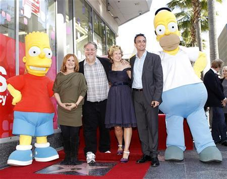 Matt Groening, creator of ''The Simpsons,'' (3rd L) poses on his star with voice actors Nancy Cartwright (2nd L), Hank Azaria (2nd R), Yeardley Smith (3rd R) and characters Homer (R) and Bart Simpson after the star was unveiled on the Walk of Fame in Hollywood, California February 14, 2012. Cartwright, Azaria and Smith are the voices of various characters in ''The Simpsons''. REUTERS/Mario Anzuoni
